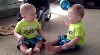 双胞胎宝宝坐在地上唠嗑