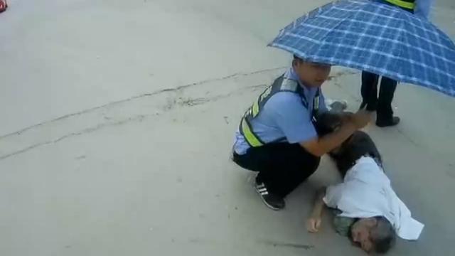 视频|老人摔伤昏迷路中间 交警烈日下为其撑伞排人墙