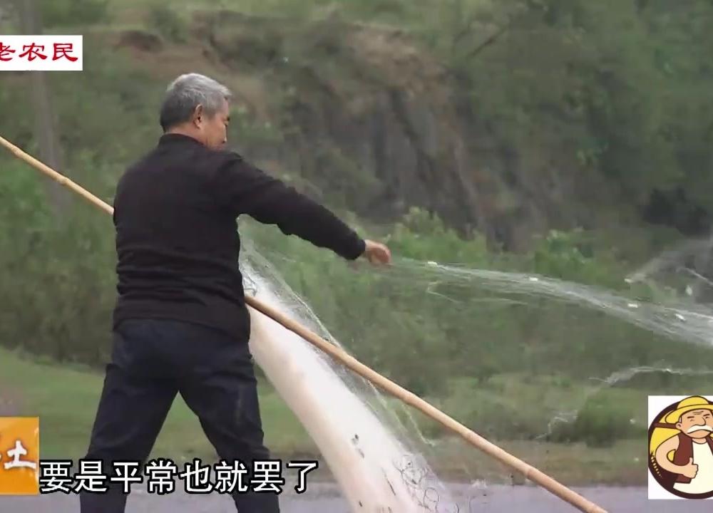 农村老爷爷在湖里捕鱼,由于下雨鱼少,一天才抓到2条鱼